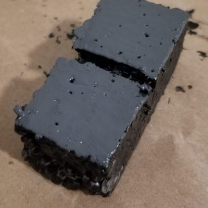 1 inch by 2 inch modular syrofoam dungeon tile with first coat of dark grey paint